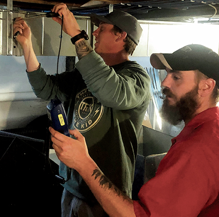 Techs trying to discover air leakage in a live duct system
